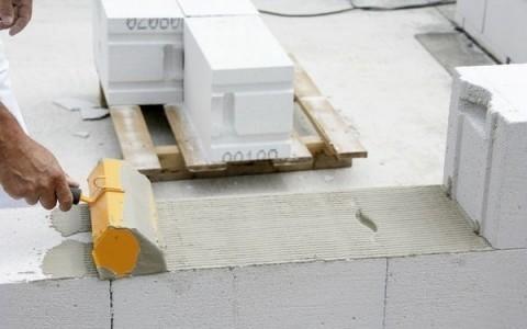 Нанесение клея на поверхность блока