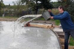 Поливка фундамента водой