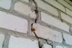 Трещина в кирпичной стене возникает из-за усадки дома, неправильной кладки.